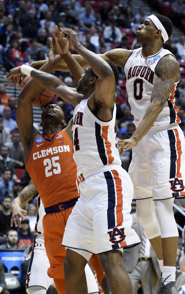 Auburn forward Horace Spencer (0) and guard Malik Dunbar (14) team up to stop a shot from Clemson forward Aamir Simms (25) during the first half of a second-round NCAA men's college basketball tournament game Sunday, March 18, 2018, in San Diego. (AP Photo/Denis Poroy)