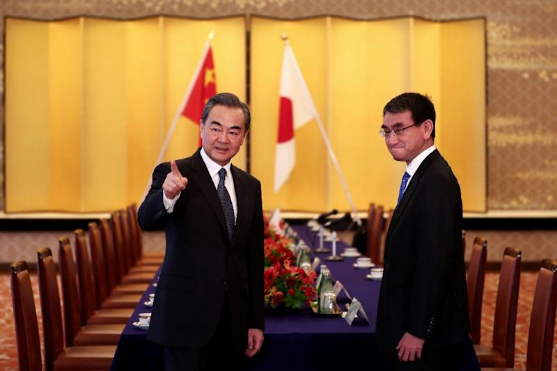 Japan's Foreign Minister Taro Kono (R) and his Chinese counterpart Wang Yi (L) arrive for their meeting in Tokyo