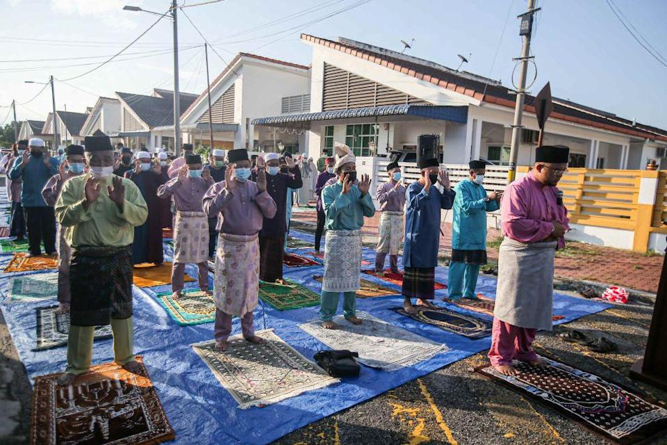 Residents of Taman Klebang Restu perform obligatory Aidilfitri prayers in front of their homes on the first day of Raya May 13, 2021. — Picture by Farhan Najib