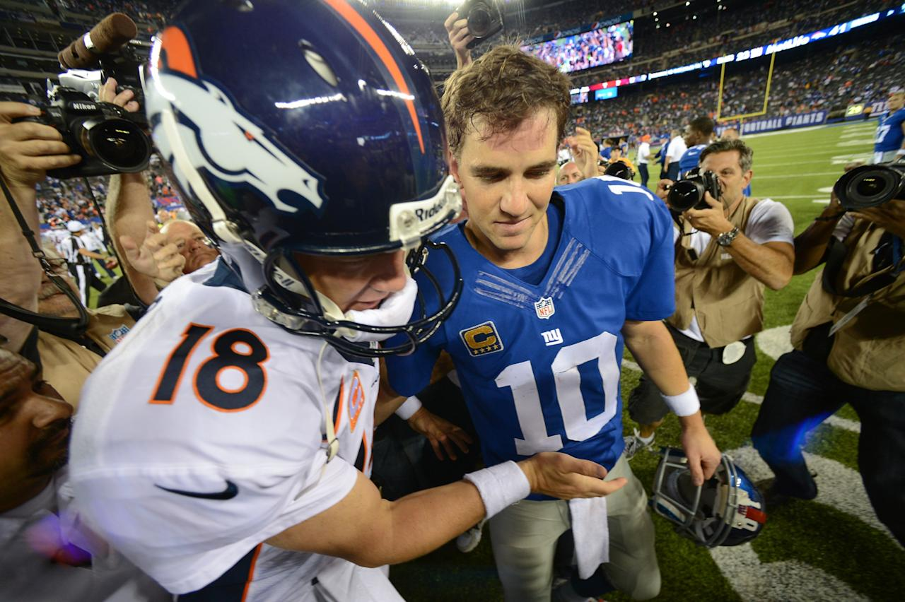 EAST RUTHERFORD, NJ - SEPTEMBER 15: Quarterback Peyton Manning #18 of the Denver Broncos and brother quarterback Eli Manning #10 of the New York Giants shake hands at the end of the Denver Broncos 41-23 win over the New York Giants at MetLife Stadium on September 15, 2013 in East Rutherford, New Jersey. (Photo by Ron Antonelli/Getty Images)