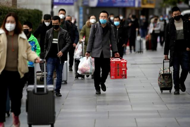FILE PHOTO: Passengers wearing masks walk outside the Shanghai railway station in Shanghai