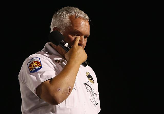 PRESCOTT, AZ - JULY 02: Prescott Fire Marshal Division Chief, Don Devendorf wipes tears from his eye as he speaks at the candlelight vigil in honor of the 19 fallen firefighters at Prescott High School on July 2, 2013 in Prescott, Arizona. 19 Granite Mountain Interagency Hotshot Crew firefighters died battling a fast-moving wildfire near Yarnell, AZ on Sunday. (Photo by Christian Petersen/Getty Images)