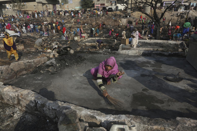CAPTION CORRECTION: CORRECTS YEAR: A woman sweeps an area of her home following a fire that gutted a neighborhood in Karachi, Pakistan, Wednesday, Jan. 22, 2020. Hundreds of huts were burnt to ashes as fire erupted making dozens of families homeless in a slum of Karachi, local media reported. (AP Photo/Fareed Khan)