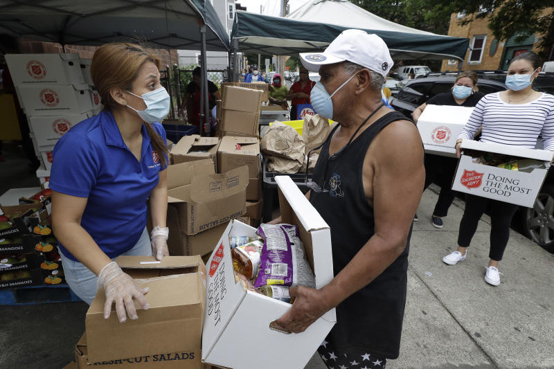 Salvation Army worker Brenda Gonzalez, of Saugus, Mass., left, distributes food to an unidentified man while others impacted by the coronavirus wait in line at a Salvation Army center, Tuesday, June 30, 2020, in Chelsea, Mass. (AP Photo/Steven Senne)