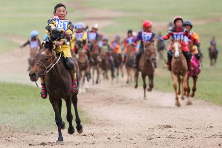Child jockeys ride their horses to the finish line during a horse race at the Mongolian traditional Naadam festival, on the outskirts of Ulaanbaatar