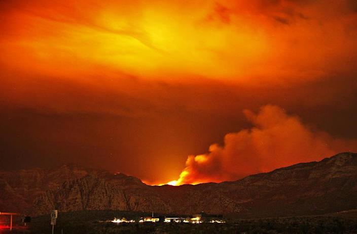 The Carpenter 1 fire burns in the mountains behind the Red Rock Conservation Area visitor center near Las Vegas early in the morning of Thursday, July 11, 2013. The fire has forced the closure of the Red Rock National Conservation Area Scenic Loop. Firefighters in the mountains near Las Vegas hoped Thursday that predicted rain showers and cooler temperatures would help them corral the massive wildfire that for 10 days charred almost 44 square miles and was still just 15 percent contained. (AP Photo/Las Vegas Review-Journal, John Locher)
