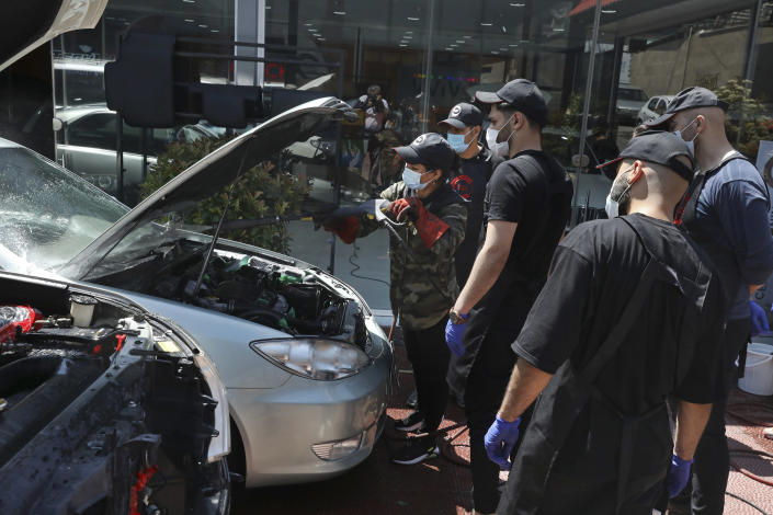 Female Iranian car detailer Maryam Roohani, left, cleans a car spraying water as her trainees watch, at a detailing shop in Tehran, Iran, Sunday, April 18, 2021. Roohani has battled skeptics and stereotypes to live out her dream of working as a professional detailer. The auto industry remains male-dominated around the world, let alone in the tradition-bound Islamic Republic. Still Iranian women, especially in the cities, have made inroads over the years. (AP Photo/Vahid Salemi)