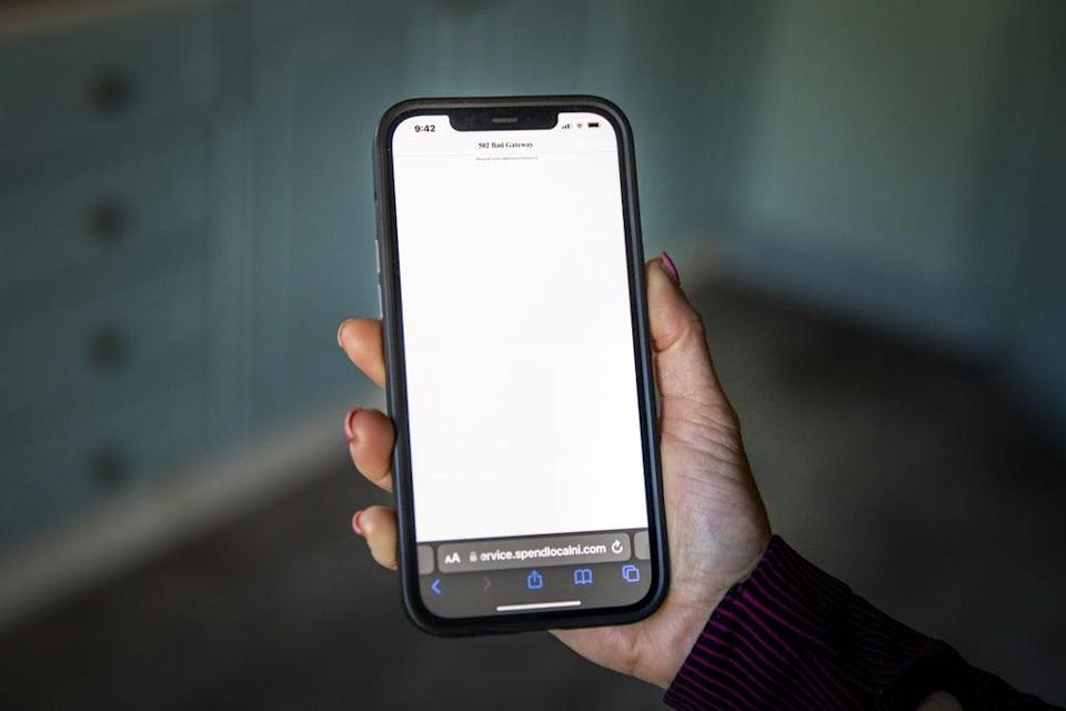 A woman using a mobile phone showing an error message after attempting to open a link to the High Street voucher scheme pre-paid card on the NI Direct website (Liam McBurney/PA) (PA Wire)