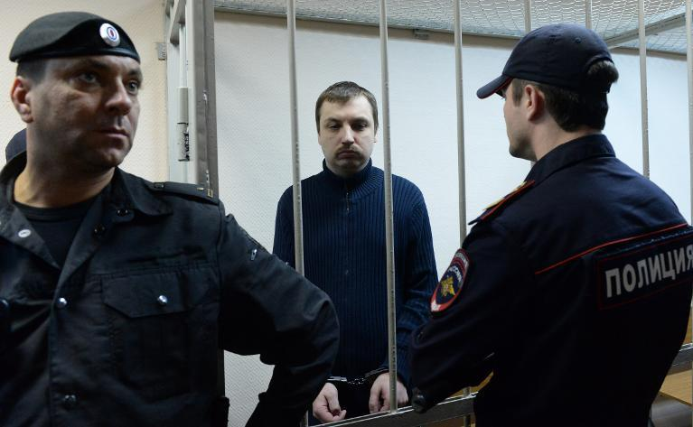 Mikhail Kosenko, an activist accused of violence at a rally on the eve of President Vladimir Putin's inauguration, stands in the defendant's cage in a court in Moscow, on October 8, 2013