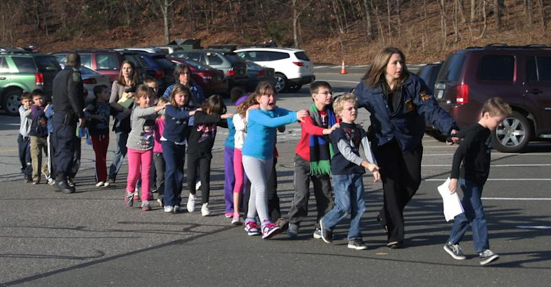 """FILE - In this Friday, Dec. 14, 2012 file photo provided by the Newtown Bee, Connecticut State Police lead a line of children from the Sandy Hook Elementary School in Newtown, Conn. after a shooting at the school. The private equity firm Cerberus will sell its stake in a firearms company that produced one of the weapons believed to have been used in the shootings at the elementary school, calling it a """"watershed event"""" in the national debate on gun control.  While saying that it's not its role to take positions or attempt to shape or influence the gun control debate, Cerberus said it is taking what action it can by selling its stake in the Freedom Group, which makes the Bushmaster rifle. (AP Photo/Newtown Bee, Shannon Hicks) MANDATORY CREDIT: NEWTOWN BEE, SHANNON HICKS"""