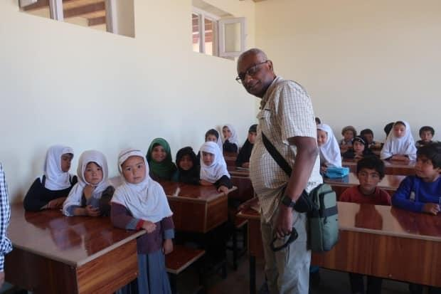 Eric Rajah in a class with students in Afghanistan. Rajah's non-profit A Better World Canada built 14 schools in the country. (Submitted by Eric Rajah - image credit)
