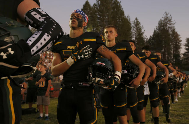 FILE - In this Aug. 23, 2019 file photo, members of the Paradise High School football team stand for the playing of the national anthem before their game against Williams High School in Paradise, Calif. Paradise, the Northern California high school football team is preparing to play for a championship one year after most of the players and coaches lost their homes to a wildfire that nearly destroyed their town. Paradise High School will face Sutter Union High School on Saturday, Nov. 30 for the Northern Section Division III championship.(AP Photo/Rich Pedroncelli, File)