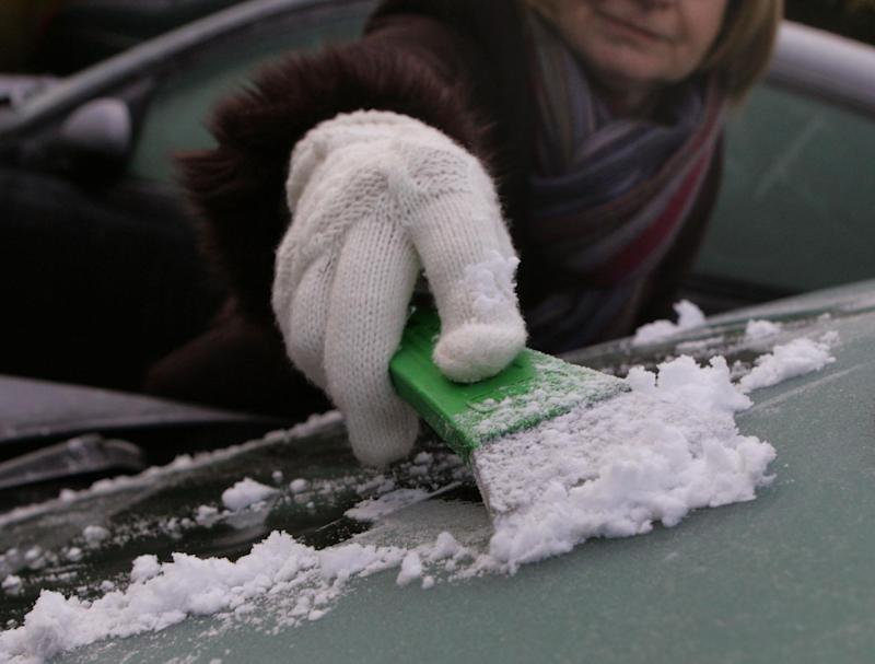 De-icing a car windscreen in Windlesham Surrey.