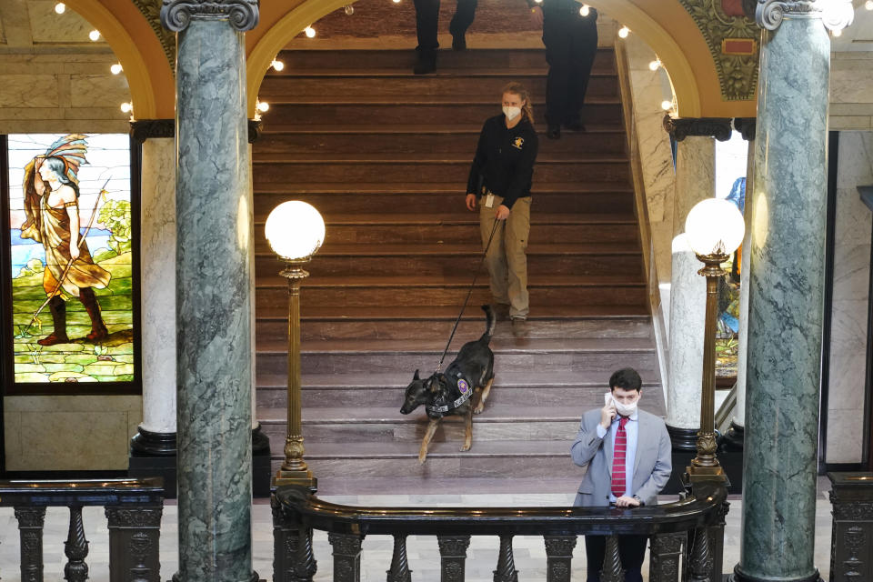 """Deputy State Fire Marshal Kayla Riggs follows the agency's explosive detection dog, """"Ringo,"""" as he walks down the steps of the third floor at the Capitol in Jackson, Miss., Thursday, Jan. 14, 2021. With the FBI warning of potential violence at all state capitols Sunday, Jan. 17, the ornate halls of government and symbols of democracy looked more like heavily guarded U.S. embassies in war-torn countries. (AP Photo/Rogelio V. Solis)"""