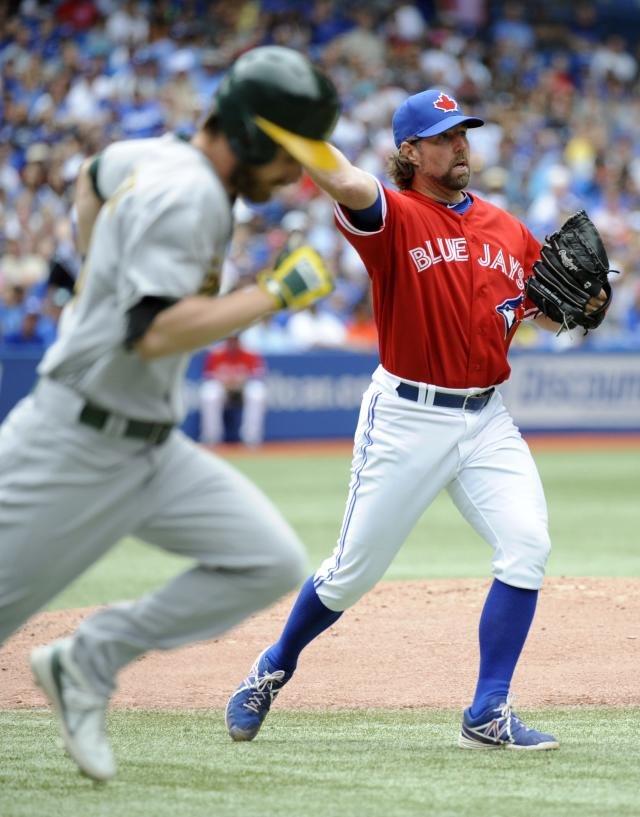 Toronto Blue Jays pitcher R.A. Dickey, right, throws to first base after Oakland Athletics' Josh Reddick laid down a bunt during the fourth inning of a baseball game on Sunday, Aug. 11, 2013, in Toronto. (AP Photo/The Canadian Press, Jon Blacker)