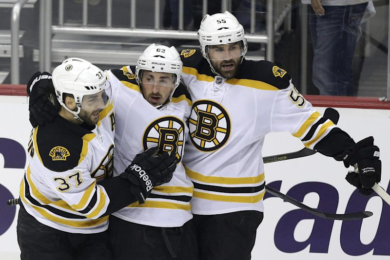 Boston Bruins' Brad Marchand, center, celebrates his goal with teammates Patrice Bergeron (37) and Johnny Boychuk (55) in the first period of Game 2 of the NHL hockey Stanley Cup playoffs Eastern Conference finals against the Pittsburgh Penguins in Pittsburgh on Monday, June 3, 2013. (AP Photo/Gene J. Puskar)