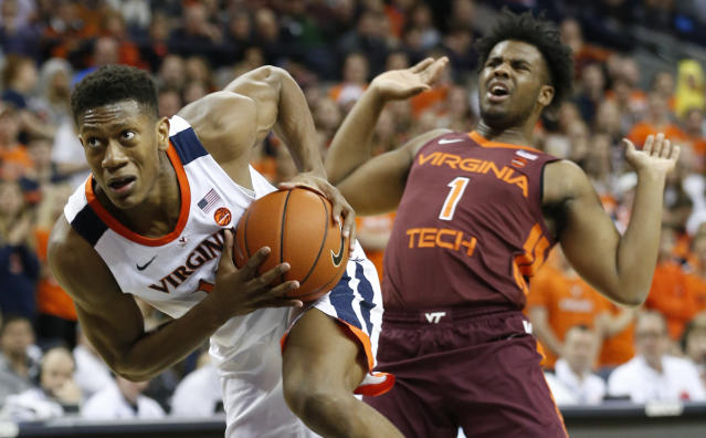 Virginia guard De'Andre Hunter (12) drives top the basket as he gets around Virginia Tech guard Isaiah Wilkins (1) during the first half of an NCAA college basketball game in Charlottesville, Va., Tuesday, Jan. 15, 2019. (AP Photo/Steve Helber)