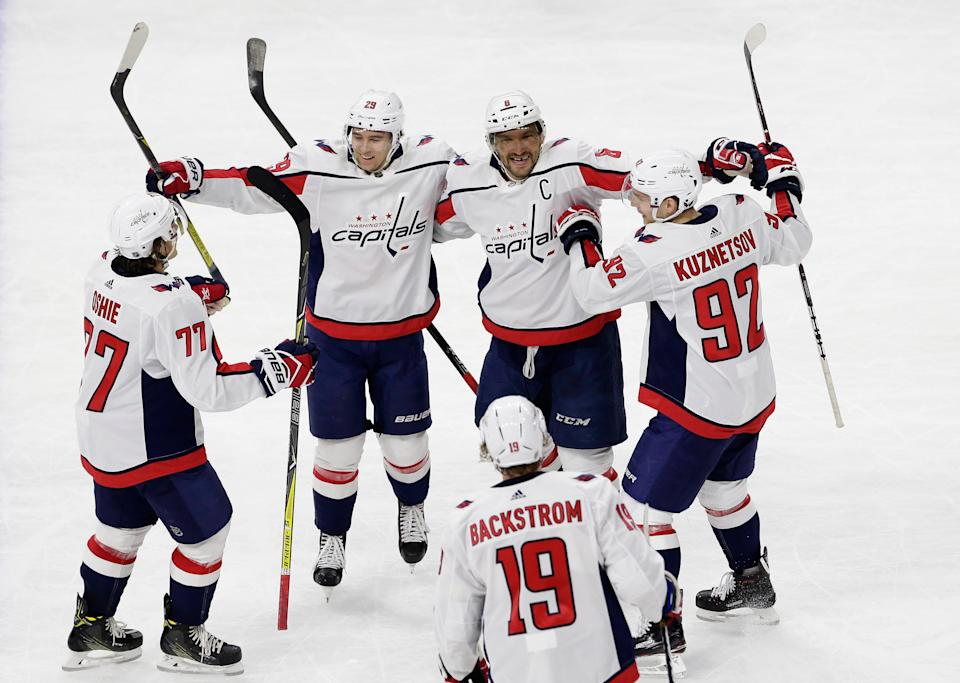 Washington Capitals' Alex Ovechkin (8), of Russia, is congratulated by Evgeny Kuznetsov (92), of Russia; Nicklas Backstrom (19), of Sweden; T.J. Oshie (77); and Christian Djoos (29) following Ovechkin's overtime goal in an NHL hockey game against the Carolina Hurricanes in Raleigh, N.C., Tuesday, Jan. 2, 2018. Washington won 5-4.