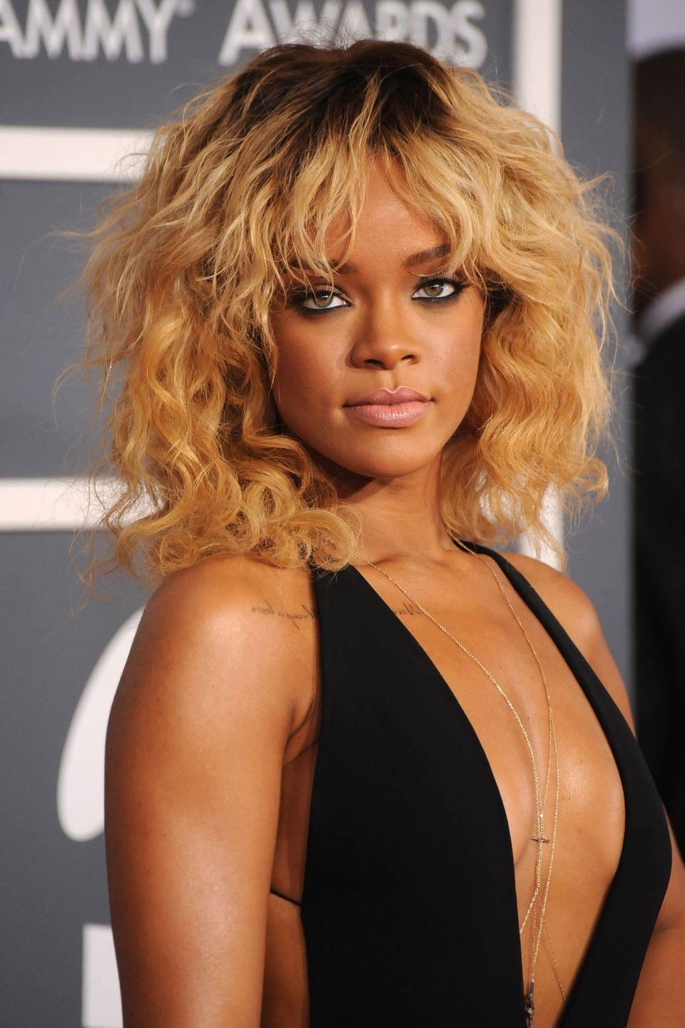 <p>Rihanna goes full blonde and wears her shaggy lob with soft curls. </p>