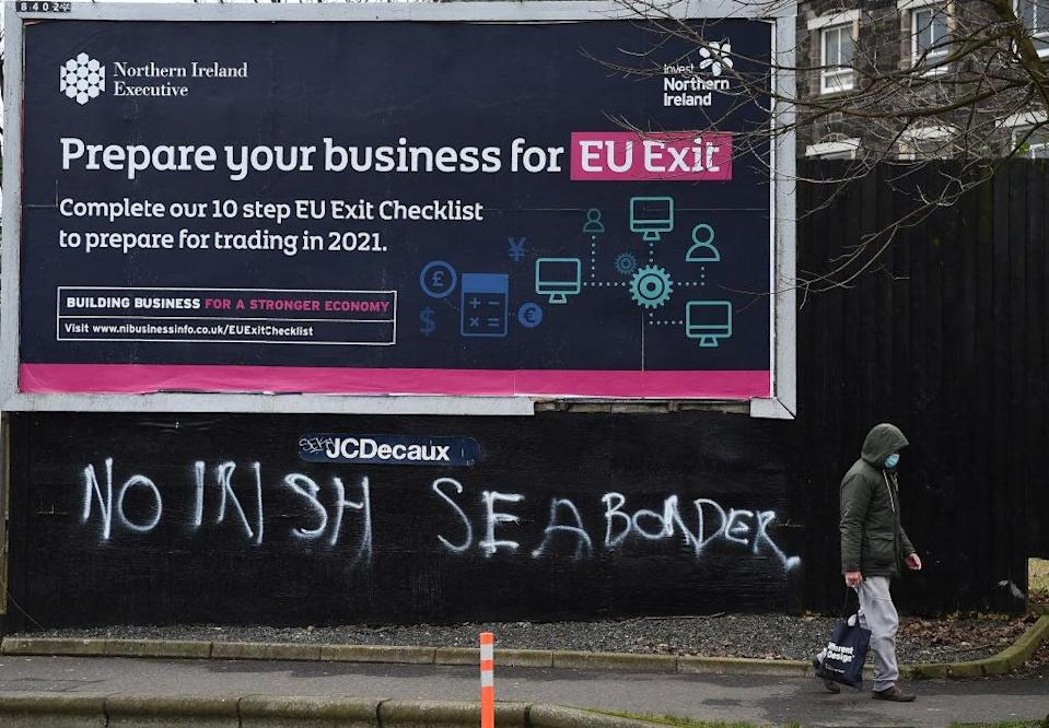 A man walks past graffiti in the loyalist Sandy row area, which reads 'No Irish sea border' under an EU Exit billboard on 30 January, 2021 in Belfast. The Police Service of Northern Ireland has been monitoring growing unionist discontent regarding the implementation of a so called Irish sea border (Getty Images)