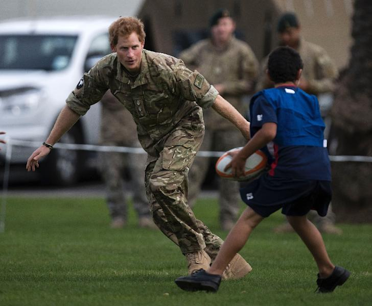 Britain's Prince Harry (L) plays a game of touch rugby with children during a visit to Linton Military Camp near Palmerston North, on May 13, 2015 (AFP Photo/Marty Melville)