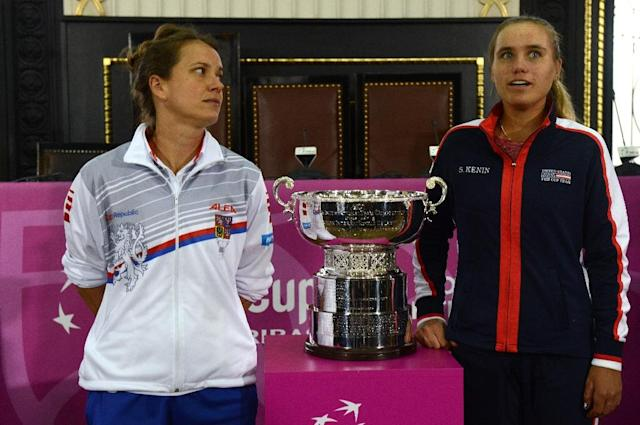 Czech Barbara Strycova (L) eyes her opponent for Saturday's opening rubber, American Sofia Kenin, as both stand next to the Fed Cup trophy which will be decided this weekend. (AFP Photo/Michal Cizek)
