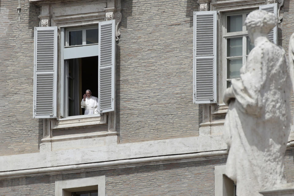 Pope Francis gives his blessing from his studio's window, overlooking St. Peter square, at the Vatican Sunday, May 17, 2020. During his weekly Sunday blessing, Pope Francis welcomed the fact that from Monday Holy Mass can be celebrated in Italy with the congregation present -- but he urged the faithful to follow the rules. ''Please, let's go ahead with the norms, the prescriptions, that they give us to safeguard the health of each of us, and of the people.'' (AP Photo/Alessandra Tarantino)