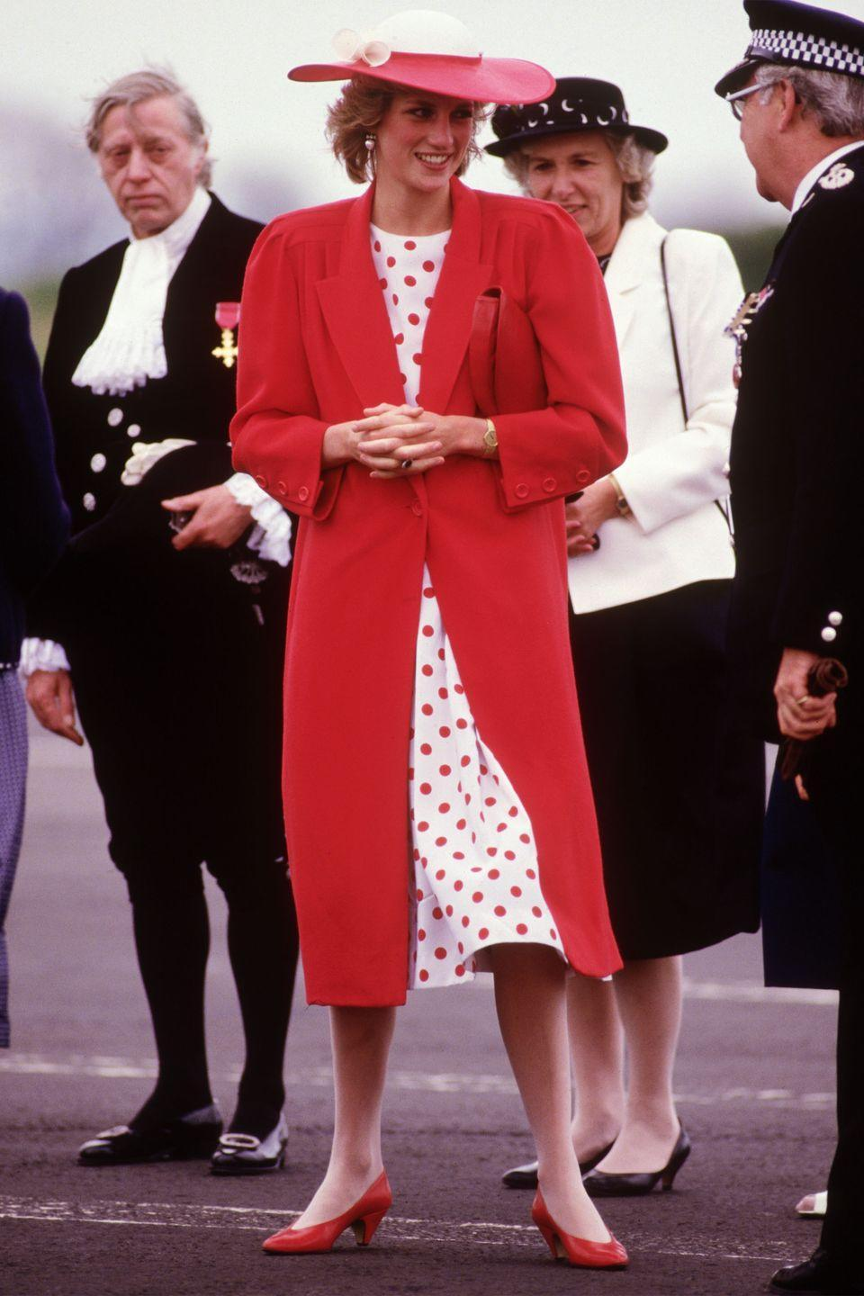 <p>In a polka-dot dress, red coat, and matching hat and shoes while visiting Newcastle. </p>