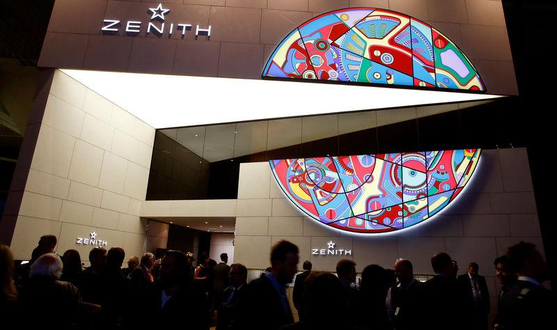 Visitors walk past the exhibition stand of Swiss watch manufacturer Zenith at the Baselworld Watch and Jewellery Show in Basel