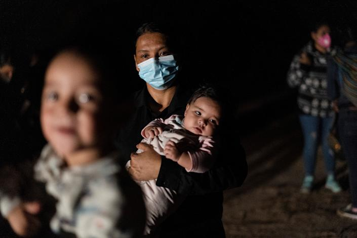 An asylum-seeking migrant mother holds her baby as she waits to be escorted by U.S. Border Patrols after crossing the Rio Grande river into the United States from Mexico in Roma, Texas, U.S., May 28, 2021. (Go Nakamura/Reuters)
