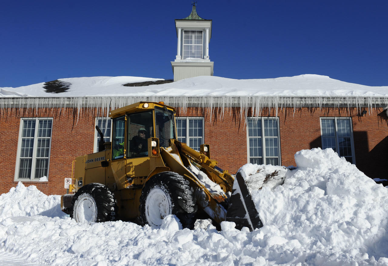 A plow clears a path outside Poquonock Elementary School in Windsor, Conn., Sunday, Feb. 10, 2013. A howling storm across the Northeast left much of the New York-to-Boston corridor covered with more than three feet of snow on Friday into Saturday morning. (AP Photo/Jessica Hill)