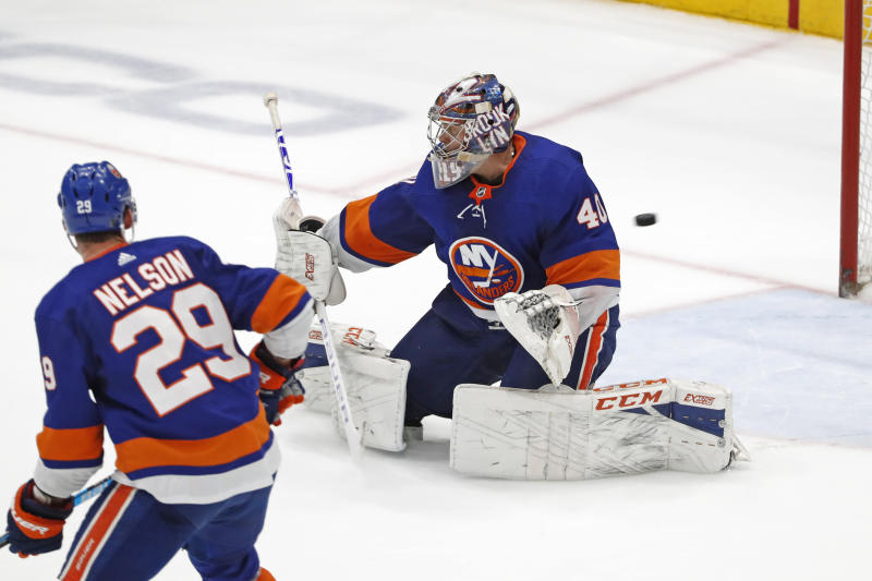 A shot by New York Rangers' Mika Zibanejad gets past New York Islanders goaltender Semyon Varlamov (40) as center Brock Nelson (29) watches in the opening minute of overtime of an NHL hockey game, Tuesday, Feb. 25, 2020, in Uniondale, N.Y. The Rangers defeated the Islanders 4-3. (AP Photo/Kathy Willens)