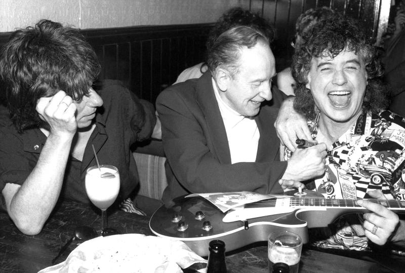 FILE - In this Nov. 6, 1987 file photo, guitar designer Les Paul, center, signs former Led Zeppelin guitarist Jimmy Page's chest after signing his guitar at a 72nd birthday party thrown for Paul by Gibson guitar company at New York's Hard Rock Cafe. Guitarist Jeff Beck, left, joined Paul and Page for the party, which drew a variety of rock music personalities. Les Paul was a renown musician also known for his innovations on the solid body electric guitar and multitrack recording. The man who helped pave the way for rock 'n' roll is finally getting a permanent exhibit on June 9, 2013 at the Waukesha County Museum in his Wisconsin hometown. (AP Photo/John Bellissimo, file)