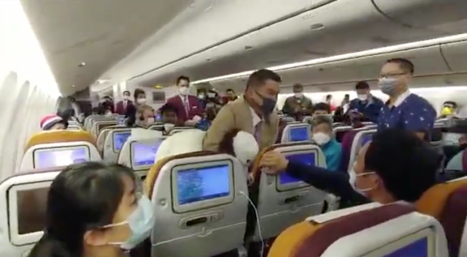 A passenger is placed in a headlock by Thai Airways staff.