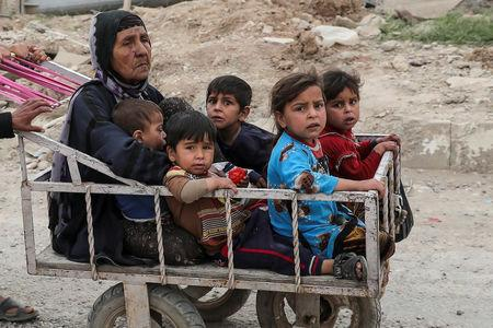A displaced Iraqi woman and children are transported in a cart as the battle between the Iraqi Counter Terrorism Service and Islamic State militants continues nearby, in western Mosul, Iraq, April 23, 2017. REUTERS/Marko Djurica
