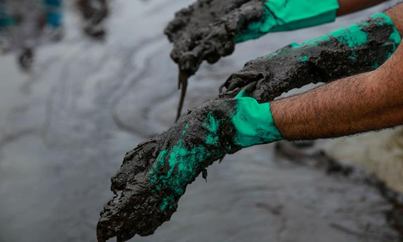 People work to remove an oil spill on Suape beach in Cabo de Santo Agostinho, Pernambuco.