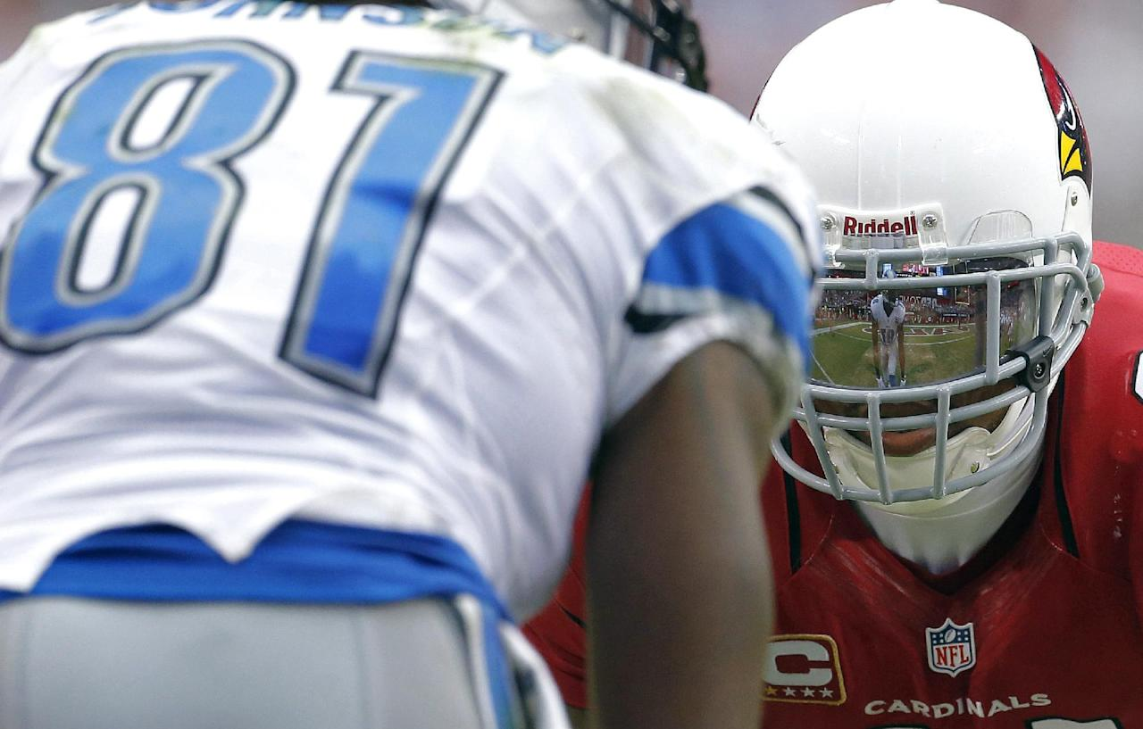 The reflection of Detroit Lions wide receiver Calvin Johnson (81) is seen in the face mask of Arizona Cardinals defensive back Tyrann Mathieu during the second half of a NFL football game, Sunday, Sept. 15, 2013, in Glendale, Ariz. (AP Photo/Darryl Webb)
