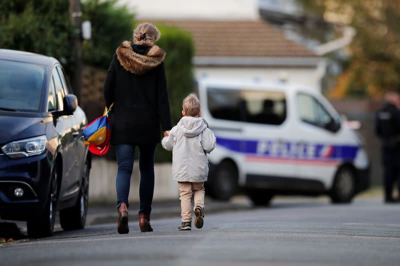 Woman holds her child by the hand on their way to the school in the area around the Bois d'Aulne college in the Paris suburb of Conflans-Sainte-Honorine