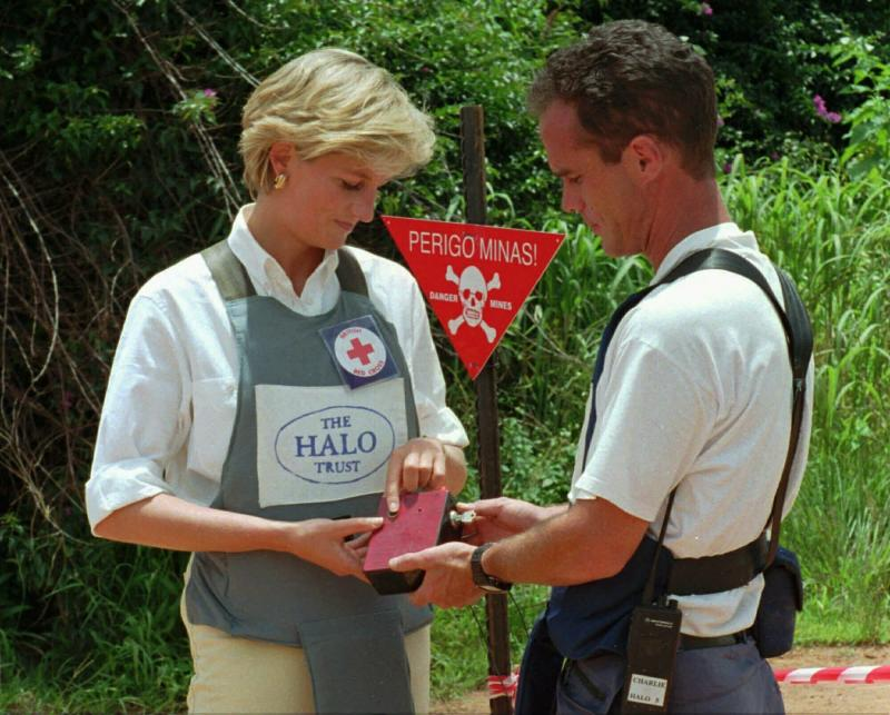 FILE - In this Jan. 15, 1997 file photo, Britain's Princess Diana uses a remote switch to trigger the detonation of some explosive ordinance dug up by mine sweepers in Huambo, Angola. Prince Harry on Friday Sept. 27, 2019, is following in the footsteps of his late mother, Princess Diana, whose walk through an active mine field in Angola years ago helped to lead to a global ban on the deadly weapons. (AP Photo/Giovanni Diffidenti, File)