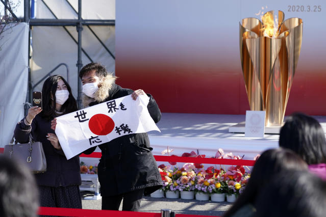 """Visitors pose with a national flag with characters reading """"Supporting the world"""" near the Olympic Flame during the Olympic """"Flame of Recovery"""" display ceremony in Iwaki, Fukushima Prefecture, northern Japan, Wednesday, March 25, 2020. IOC President Thomas Bach has agreed """"100%"""" to a proposal of postponing the Tokyo Olympics for about one year until 2021 because of the coronavirus outbreak. (AP Photo/Eugene Hoshiko)"""