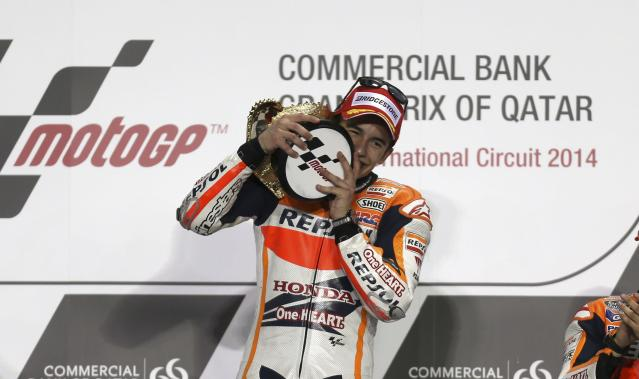 Honda MotoGP rider Marc Marquez of Spain celebrates on the podium after winning the Qatar MotoGP Grand Prix at the Losail International circuit in Doha March 23, 2014. REUTERS/Stringer (QATAR - Tags: SPORT MOTORSPORT)