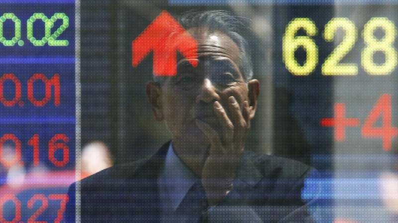 A man is reflected on the electronic board of a securities firm in Tokyo, Monday, April 22, 2013. Asian markets traded higher Monday, with Tokyo stock markets heading close to a five-year high after a meeting of global finance leaders lent support to Japan's aggressive monetary policy. (AP Photo/Koji Sasahara)