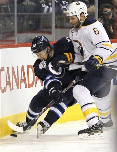 Winnipeg Jets' Bryan Little (18) and Buffalo Sabres' Mike Weber (6) fight for the puck against the boards during second-period NHL hockey game action in Winnipeg, Manitoba, Thursday, Jan. 19, 2012. (AP Photo/The Canadian Press, John Woods)