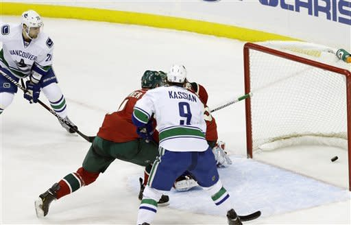 Vancouver Canucks' Chris Higgins, left top, watches his power-play goal off Minnesota Wild goalie Niklas Backstrom, of Finland, in the first period of an NHL hockey game on Thursday, Feb. 7, 2013, in St. Paul, Minn. (AP Photo/Jim Mone)