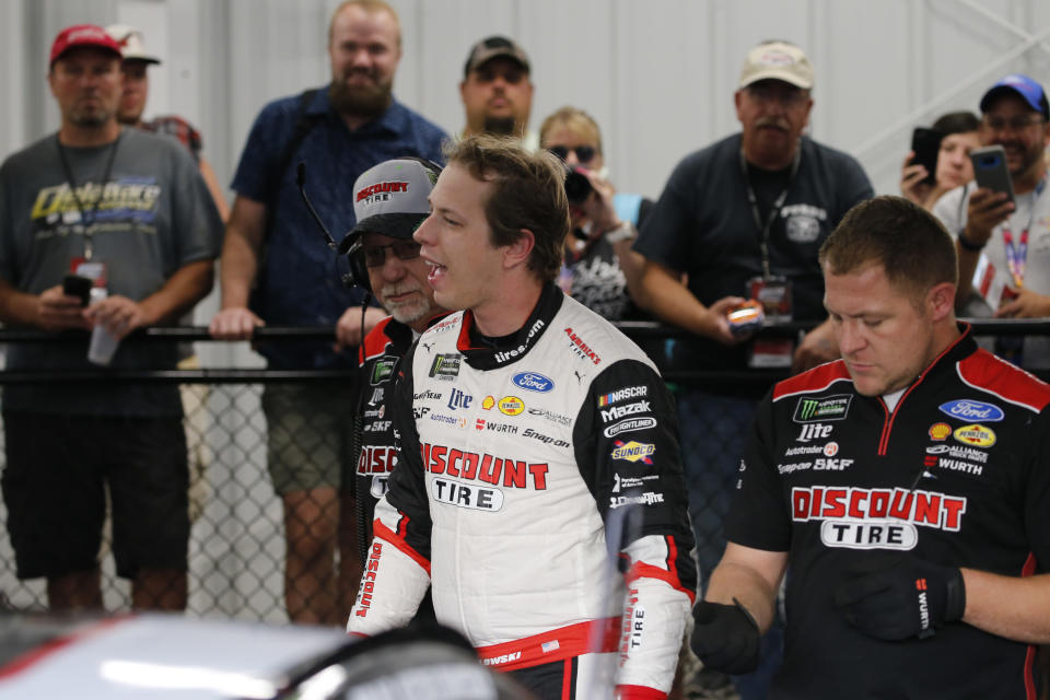 Brad Keselowski, front center, smiles in the garage after winning the pole for the NASCAR Cup Series auto race at Richmond Raceway in Richmond, Va., Friday, Sept. 20, 2019. (AP Photo/Steve Helber)