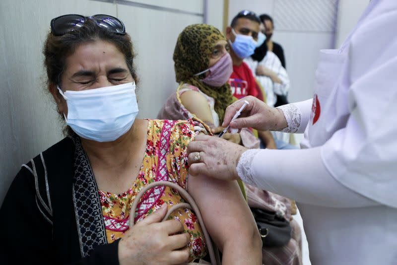 A woman receives the COVID-19 vaccine at a vaccination center in Tunis