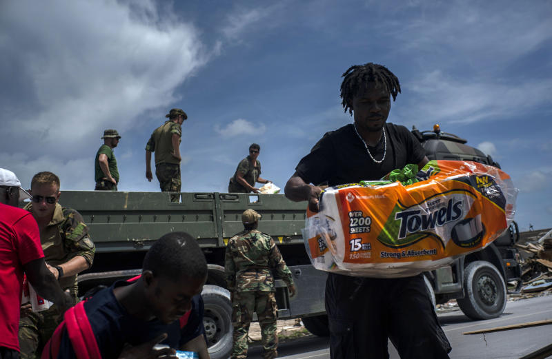 Locals receive help from Dutch soldiers in the aftermath of Hurricane Dorian in Abaco, Bahamas, Monday, Sept. 16, 2019. Dorian hit the northern Bahamas on Sept. 1, with sustained winds of 185 mph (295 kph), unleashing flooding that reached up to 25 feet (8 meters) in some areas. (AP Photo/Ramon Espinosa)