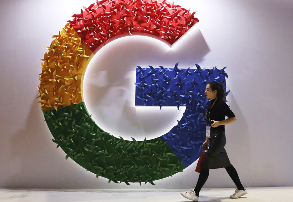 FILE - In this Monday, Nov. 5, 2018 file photo, a woman walks past the logo for Google at the China International Import Expo in Shanghai. By U.S. standards, the Justice Department's move to sue Google this week for abusing its dominance in online search and advertising was a bold move. But it treads on ground already broken years before by EU officials in Brussels. (AP Photo/Ng Han Guan, File)