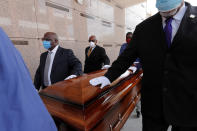 FILE - In this April 22, 2020, file photo, pallbearers, who were among only 10 allowed mourners, walk the casket for internment at the funeral for Larry Hammond, who died from the coronavirus, at Mount Olivet Cemetery in New Orleans. Government health officials say Native Americans, Latinos and Black people are two to three times more likely than whites to die of COVID-19. (AP Photo/Gerald Herbert, File)