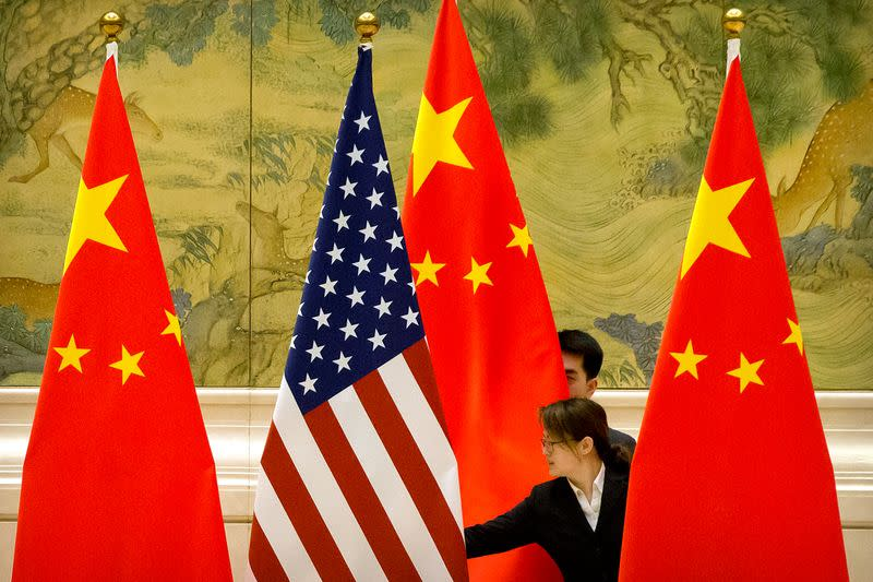 FILE PHOTO: Chinese staff members adjust U.S. and Chinese flags before the opening session of trade negotiations between U.S. and Chinese trade representatives in Beijing
